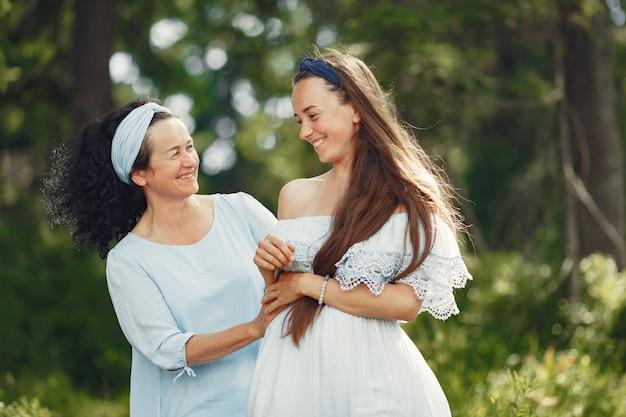 Femmes dans une forêt d'été. dame en robe bleue. famille posant et embrassant.