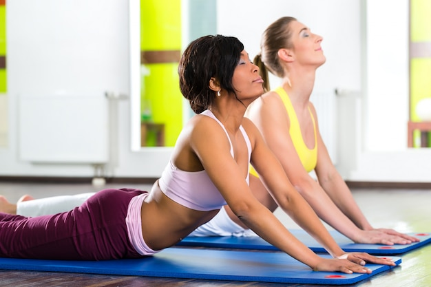 Femmes dans le gymnase faisant du yoga pour la forme