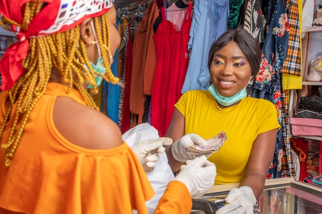 Femmes dans un magasin local effectuant des transactions en espèces