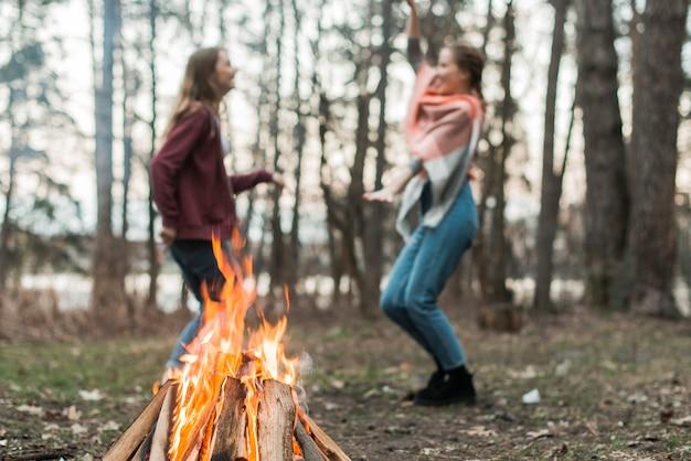 Femmes dansant autour d'un feu de joie