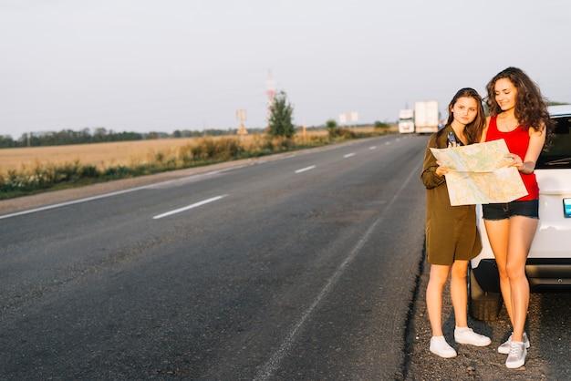 Femmes debout près d'une voiture blanche avec carte