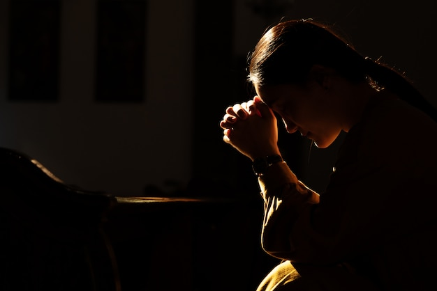 Les femmes déprimées assis dans l'église à faible luminosité et priant, concept de la journée internationale des droits de l'homme