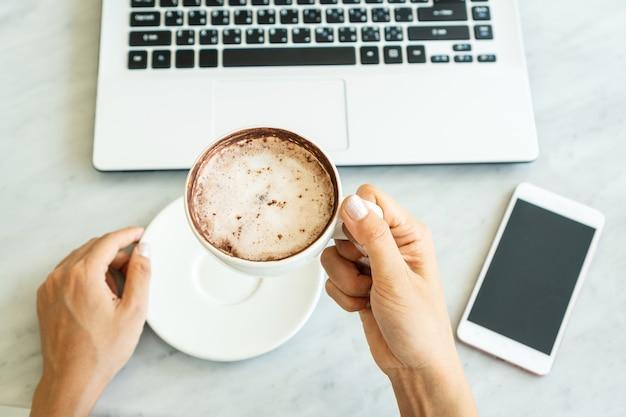 Les femmes détiennent une tasse de café tout en regardant un ordinateur portable dans un café.