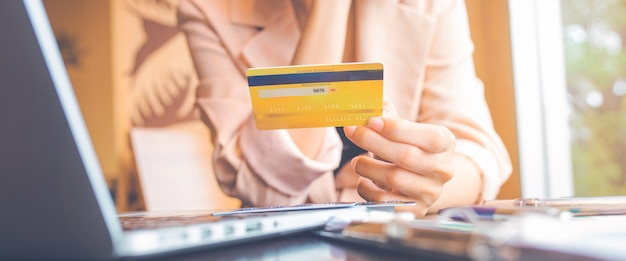 Les femmes détiennent trois cartes de crédit pour faire leurs achats en ligne avec un ordinateur portable. pour la bannière web.