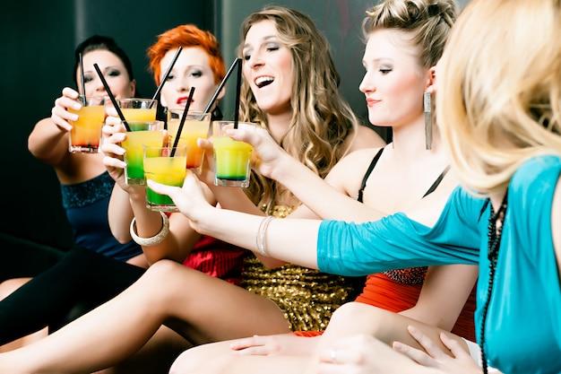 Femmes en discothèque ou disco buvant des cocktails