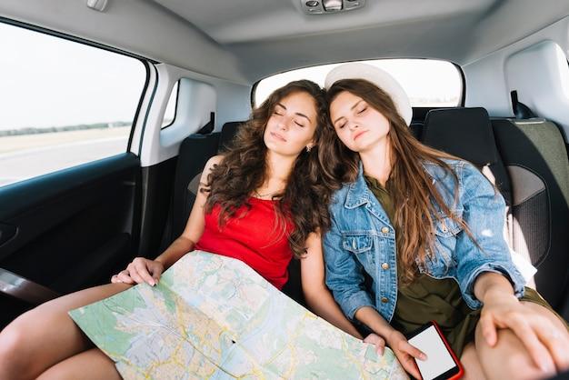Femmes dormant dans une voiture