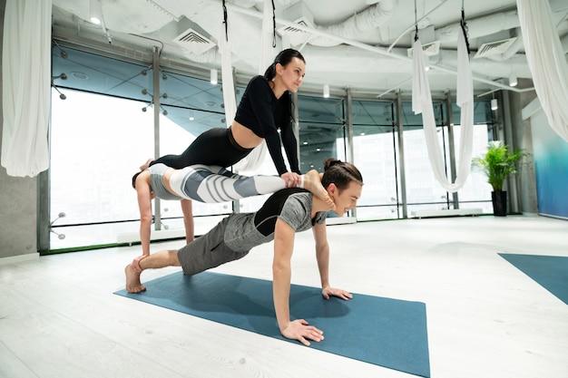 Femmes sur le dos. homme fort tenant deux femmes minces et en forme sur le dos tout en pratiquant le yoga fitness