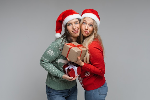Des femmes drôles en chapeaux de noël rouges et blancs tiennent des cadeaux les unes pour les autres et posent pour la caméra