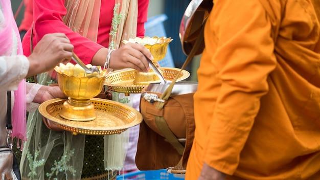 Les femmes du village mon et les visiteurs en tenue traditionnelle offrent de la nourriture au bol de mendicité du moine bouddhiste tôt le matin dans le district de sangkhlaburi, à kanchanaburi, en thaïlande. activité touristique réputée.