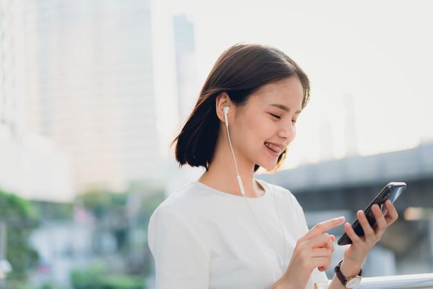 Les femmes écoutent de la musique avec un casque blanc.