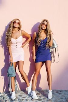 Femmes élégantes et chics posant dans des lunettes de soleil et avec des sacs à main bleus