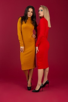 Femmes élégantes en robe tricotée de mode automne hiver jaune et rouge posant isolé sur mur rouge