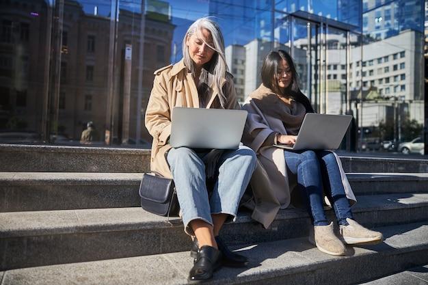 Femmes élégantes travaillant sur des ordinateurs portables dans la rue
