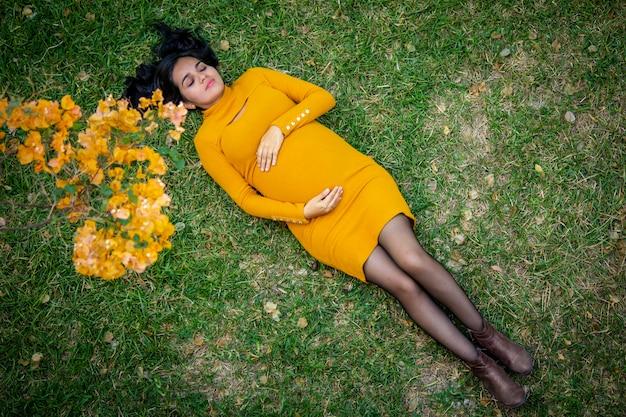 Femmes enceintes d'amérique latine allongées dans un champ de fleurs jaunes