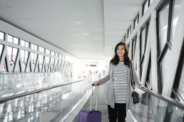 Les femmes enceintes asiatiques tirent des valises en passant devant l'escalator