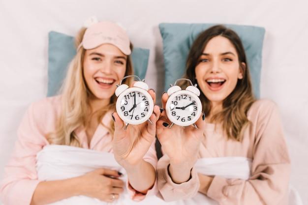 Femmes enthousiastes au lit montrant des horloges