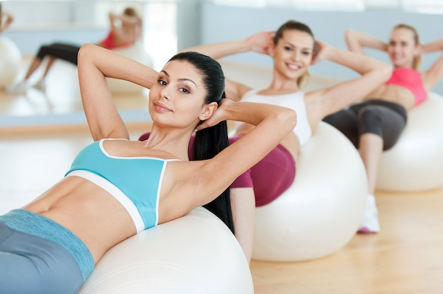 Les femmes entraînent leurs abdos. trois belles jeunes femmes en vêtements de sport s'exerçant sur des ballons de fitness
