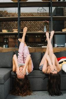Les femmes à l'envers couvrant leur visage sur un canapé