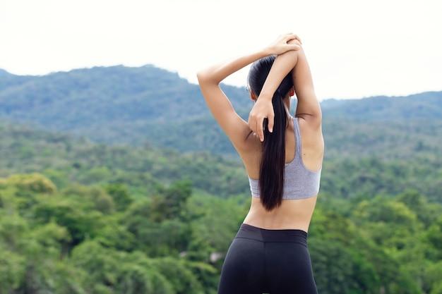 Femmes étirant les bras et respirer l'air frais au milieu de la nature tout en faisant de l'exercice. concept de séances d'entraînement et de modes de vie. thème de la vie heureuse et de la santé. vue arrière