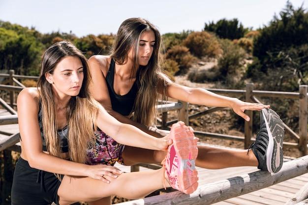 Femmes, étirement jambes, sur, jetée