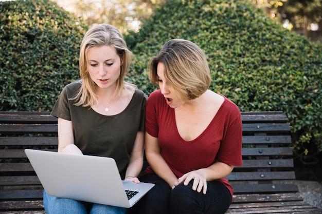 Femmes étonnées à l'aide d'ordinateur portable dans le parc