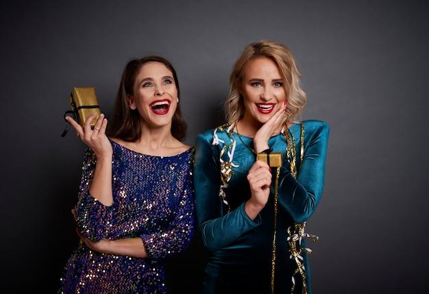 Femmes excitées tenant des cadeaux en or