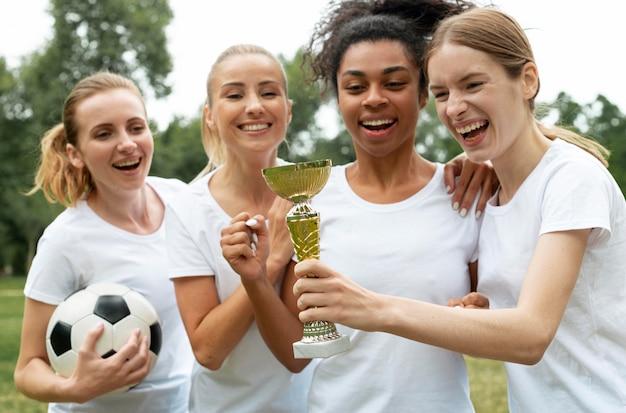 Femmes excitées tenant la coupe des gagnants