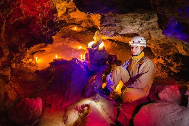 Les femmes explorent la magnifique grotte de pierre mlynky en ukraine une lumière multicolore brille sur les pierres ext...