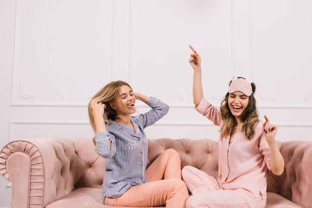 Femmes extatiques en pyjama assis sur un canapé