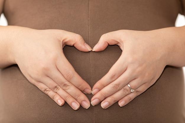 Les femmes fabriquées à la main sont asiatiques en forme de coeur sur le ventre de femme enceinte