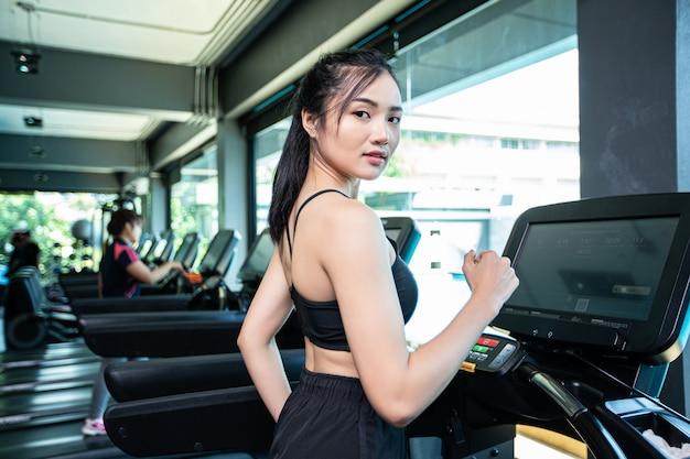 Femmes faisant du jogging sur le tapis roulant dans la salle de sport