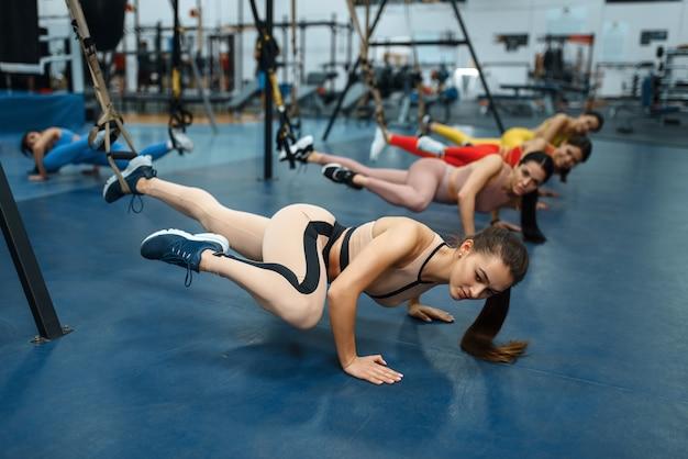 Femmes faisant des exercices d'étirement dans une salle de sport