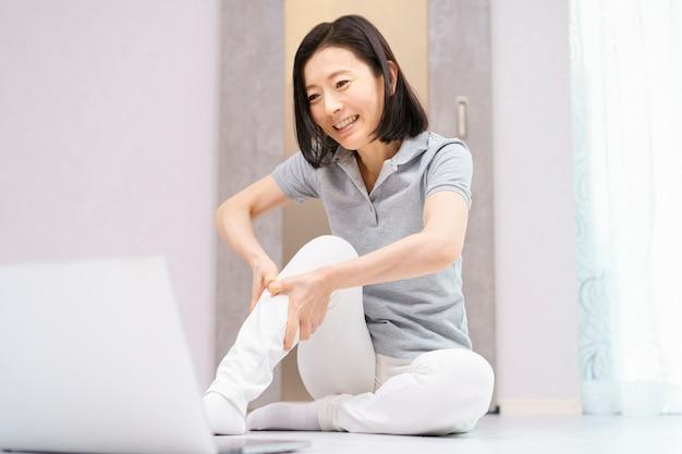 Les Femmes Faisant Des Exercices Légers Tout En Regardant Un Ordinateur Photo Premium