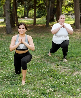 Femmes faisant des fentes dans le parc