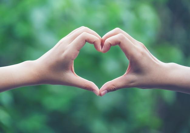 Femmes faisant des formes de coeur avec leurs mains