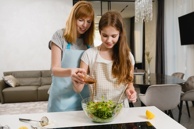 Les femmes de la famille versent la vinaigrette ensemble à l'intérieur