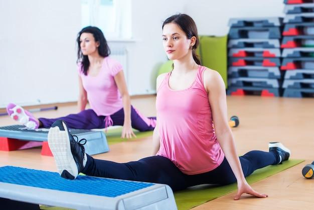 Femmes flexibles qui étirent les jambes avec des plates-formes de marche aérobie.