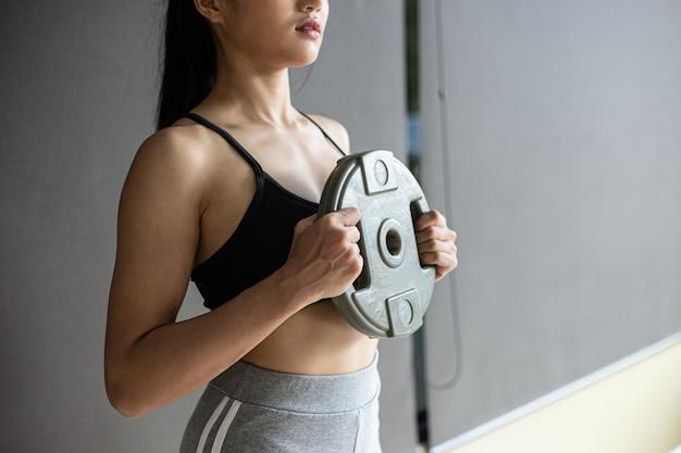Les femmes font de l'exercice avec des disques d'haltères dans la poitrine.