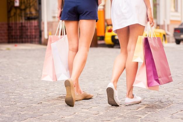 Les femmes font leurs courses. vue arrière de deux belles jeunes femmes portant des sacs à provisions en marchant le long de la rue