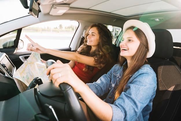 Femmes gaies conduisant la voiture