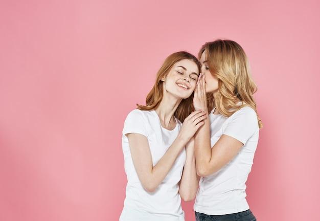 Des femmes gaies en t-shirts blancs étreignent le style de vie de socialisation fond rose glamour. photo de haute qualité