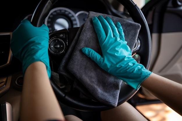 Les femmes avec des gants verts nettoyant le volant se bouchent
