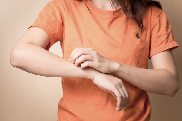 Les femmes griffent le bras qui démange avec la main.
