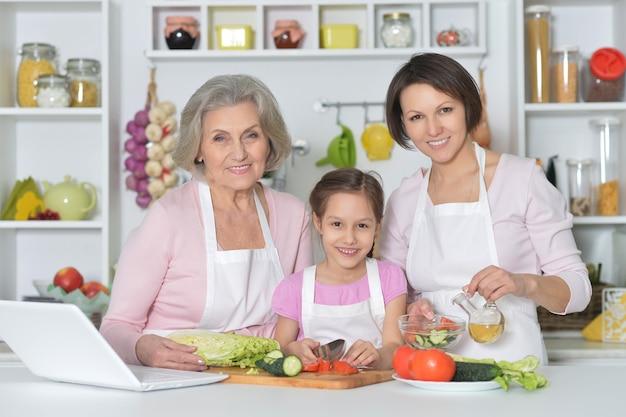 Femmes heureuses avec la petite fille faisant cuire dans la cuisine