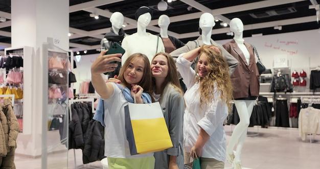 Femmes heureuses prenant selfie après le shopping. filles souriantes. ils posent pour des photos, prennent leurs mains sur les cheveux, le visage. ayez de nombreux sacs à provisions colorés.