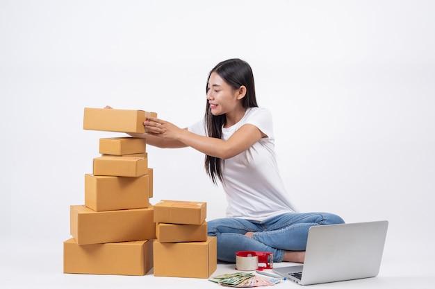 Des femmes heureuses qui commandent des produits à des clients et à des propriétaires d'entreprise qui travaillent à la maison sur un fond blanc