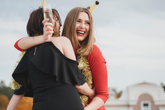 Femmes heureuses en robes rouges et noires faisant la fête sur le toit