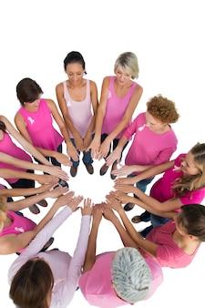 Des femmes heureuses se sont jointes en cercle et se regardent en portant du rose pour le cancer du sein