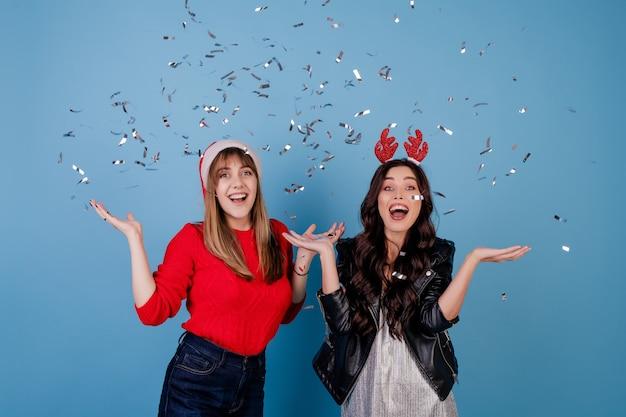 Femmes heureux avec des confettis d'argent dans l'air portant chapeau de noël isolé sur bleu