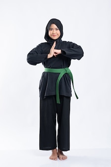 Les femmes hijab portant des uniformes de pencak silat avec des ceintures vertes effectuent des gestes de respect
